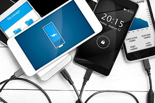 Foto em detalhe de 4 smartphones sobre uma mesa. Cada um deles está conectado ao seu cabo de bateria