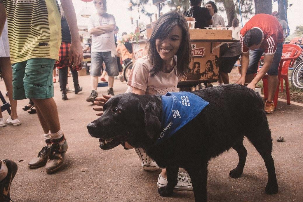 Foto de uma mulher agachada acariciando um cão guia. Ela sorri enquanto interage com o cachorro.