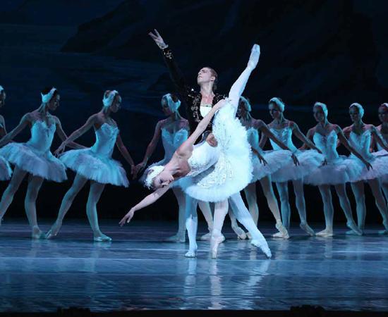 Foto de dois bailarinos. Um homem e uma mulher em um trecho do espetáculo O lago dos cisnes