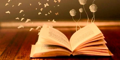 Foto de um livro aberto sobre uma mesa, dele saem ilustrações de rosa, borboletas e pássaros.