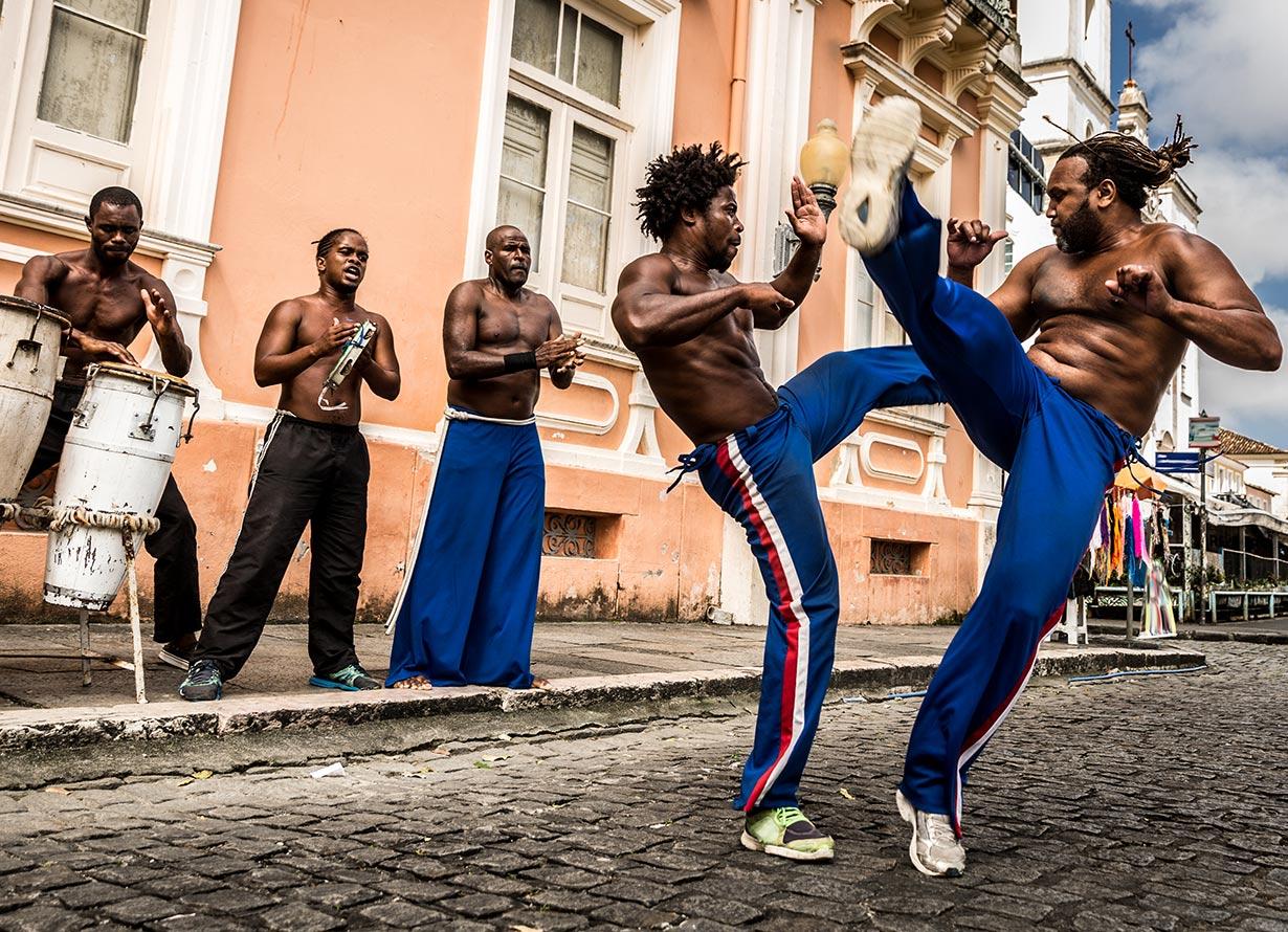 Foto de dois homens jogando capoeira em uma rua em Salvador. Ao lado, há 4 homens tocando instrumentos musicais (crédito: filipefrazao – iStock)