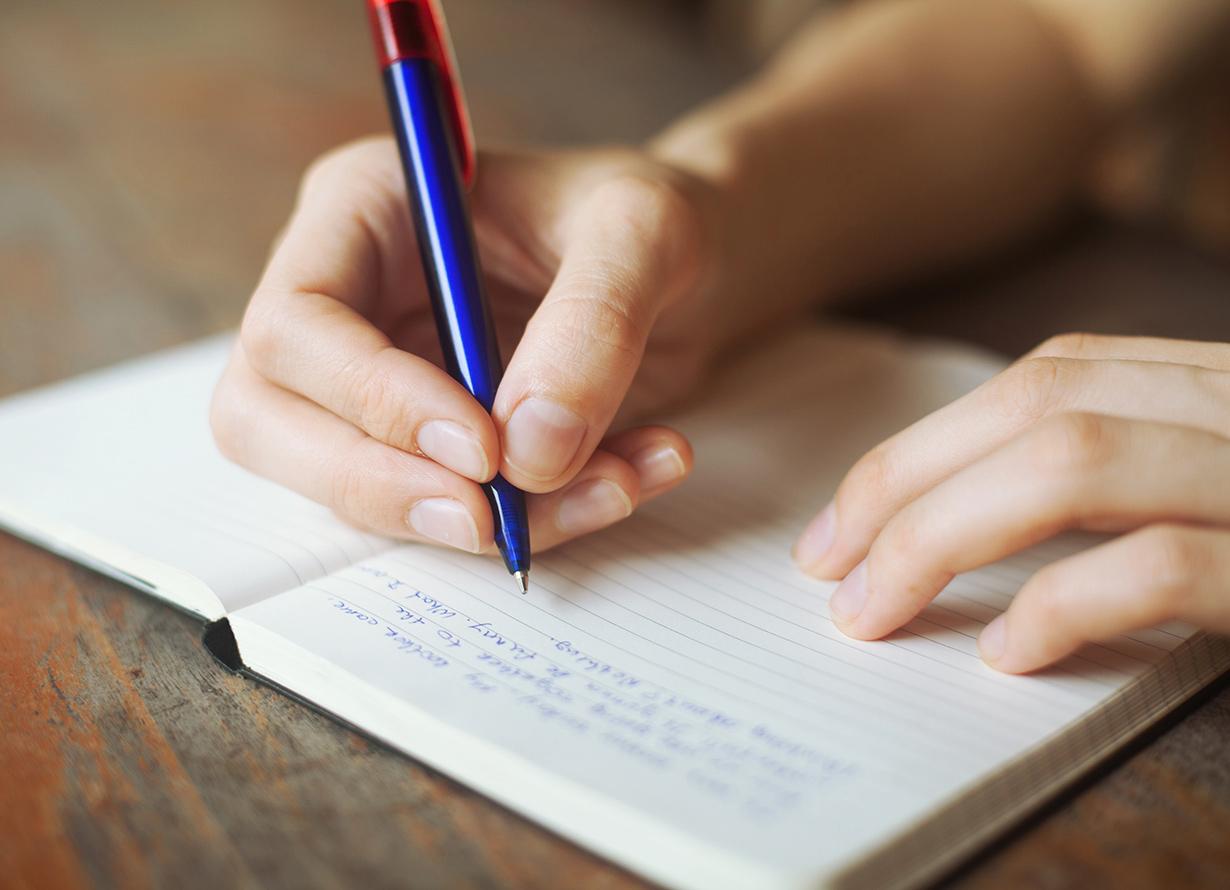 Foto em detalhe de mão escrevendo um caderno com uma caneta azul (crédito: anyaberkut – iStock)