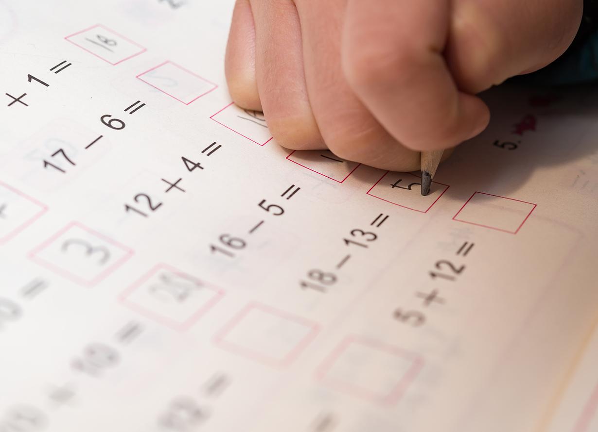 Foto em detalhe de mão preenchendo a lápis uma folha com contas matemáticas de subtração e adição (crédito: Freer Law – iStock)