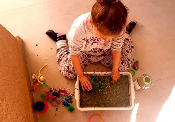 Foto vista de cima de uma menina sentada no chão brincando com uma caixa cheia de areia.