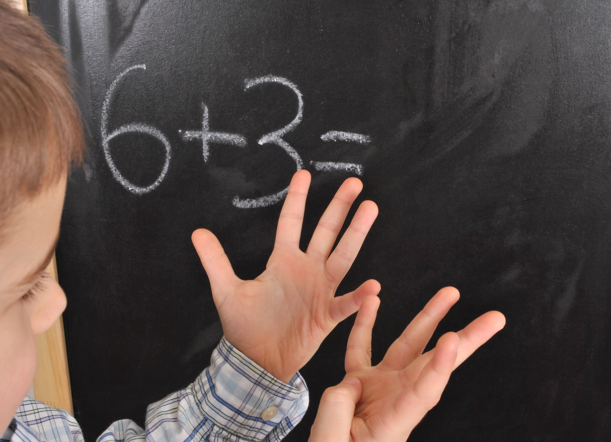Foto em detalhe de um garoto fazendo conta usando os dedos. Na lousa, atrás dele, há a conta 6+3 escrita (crédito: kilukilu – iStock)