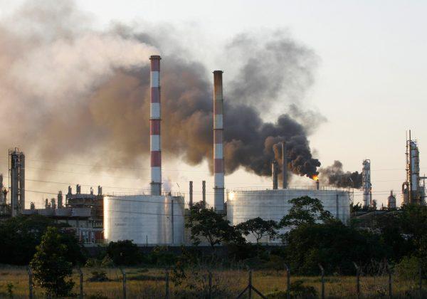 Foto de uma fábrica, contendo torres de resfriamento com fumaça preta saindo delas.
