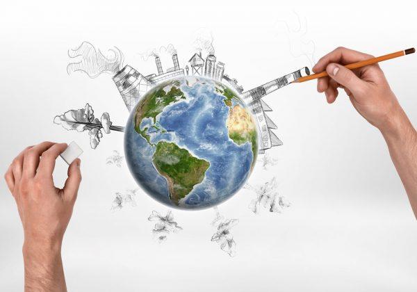 Arte de um par de mãos desenhando em uma folha, que contém um globo terrestre colorido e sobre ele, rascunhos à lápis de indústrias e árvores.