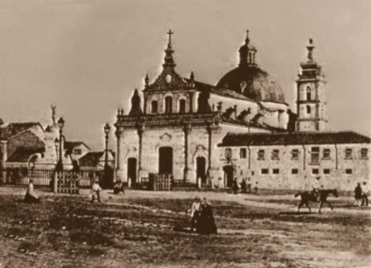 Gravura antiga de uma praça, com pessoas passando. Ao fundo há uma igreja.