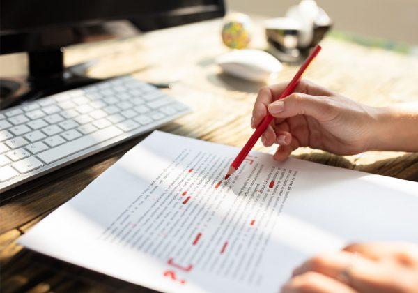 Foto de uma mesa, contendo um teclado e uma folha de papel com um texto impresso. Um par de mãos grifa, de vermelho, trechos do texto.