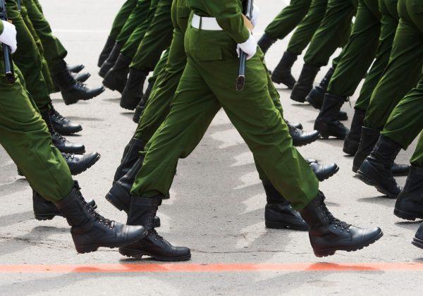 Foto das pernas de um batalhão marchando, todos usam calças verdes e botas pretas.