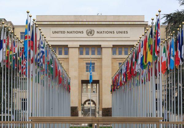 Foto da entrada do prédio da ONU com duas fileiras com bandeiras de diversos países