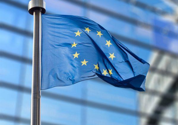 Foto da bandeira da União Europeia. Ela é azul e tem 12 estrelas amarelas formando um círculo