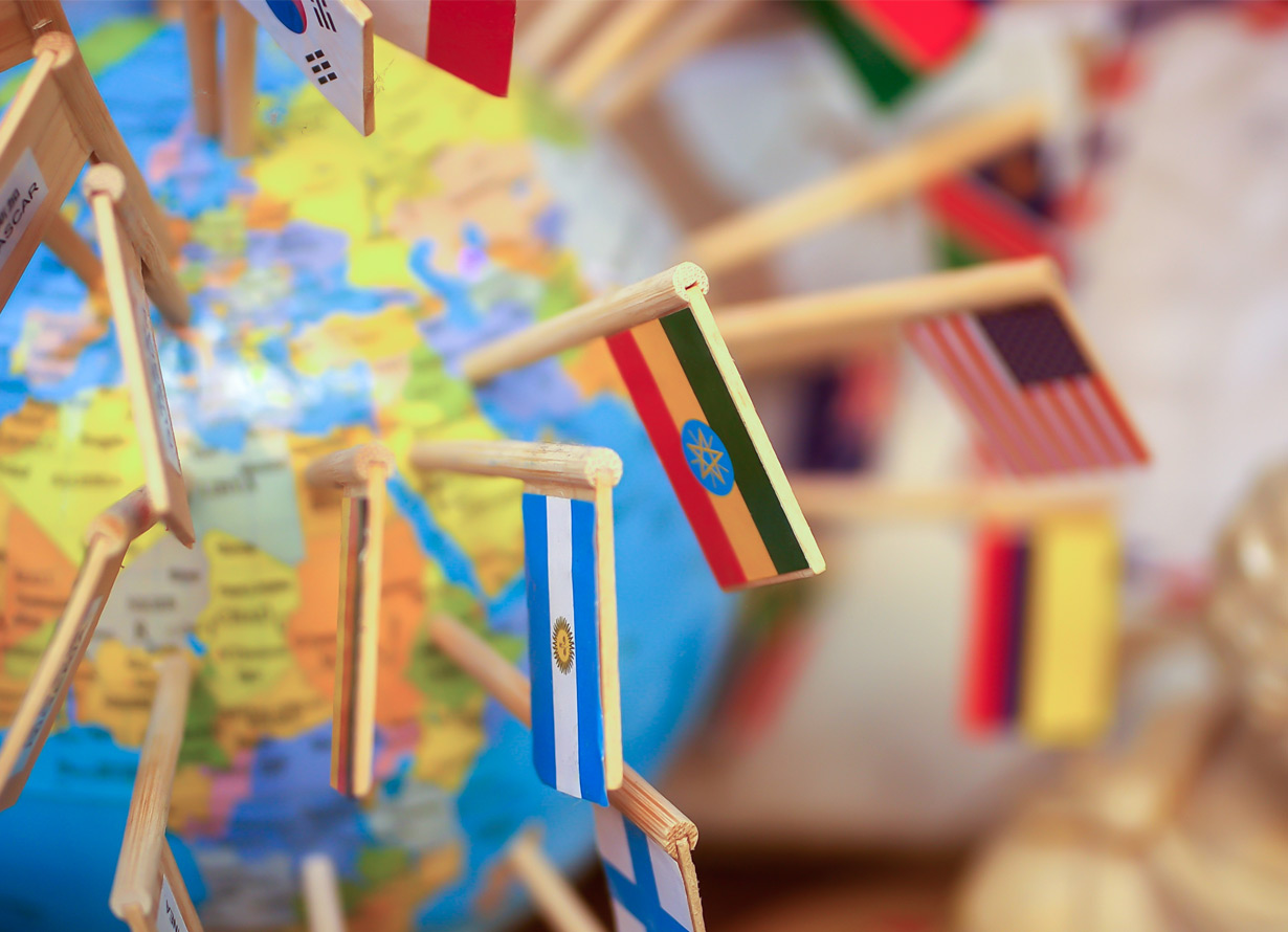 Foto em detalhe de um globo terrestre com diversas bandeiras em palitos de madeira espetadas nele