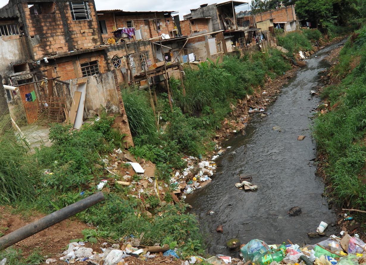 Foto de um córrego a céu aberto com lixo dentro e casas simples em sua margem
