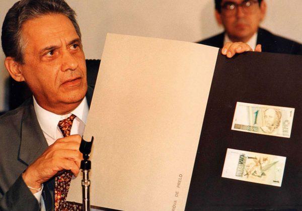 Foto, antiga, de Fernando Henrique Cardoso segurando uma pasta preta com uma duas notas de um real coladas nela, frente e verso.
