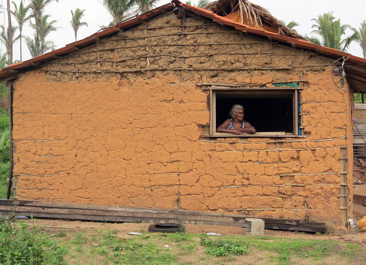 Foto de uma senhora na janela de uma casa simples