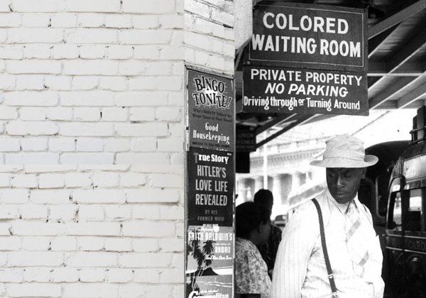 """Foto antiga, em preto e branco, de um homem negro parado em uma estação de trem. Sobre ele, há uma placa com o texto """"colored waiting room""""."""