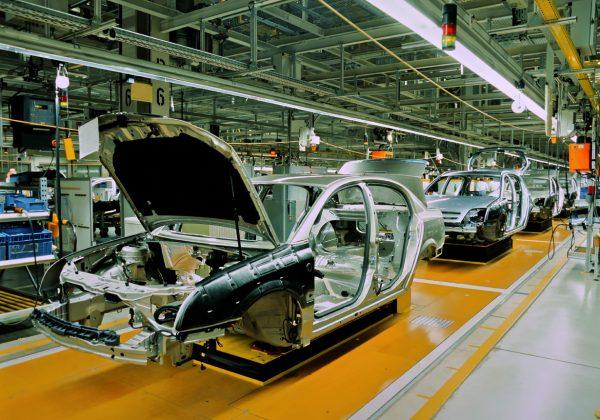 Foto de uma linha de montagem de carros, contendo a carcaça em fila de alguns automóveis cinzas. Ao fundo, há maquinários.