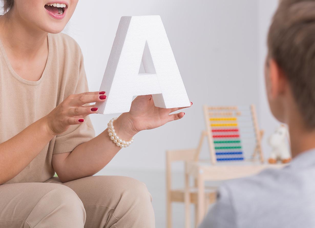 Foto em detalhe de uma mulher de boca aberta, como se estivesse falando, segurando uma letra A nas mãos. No canto direito, há uma criança de costas olhando para ela (crédito: KatarzynaBialasiewicz – iStock)