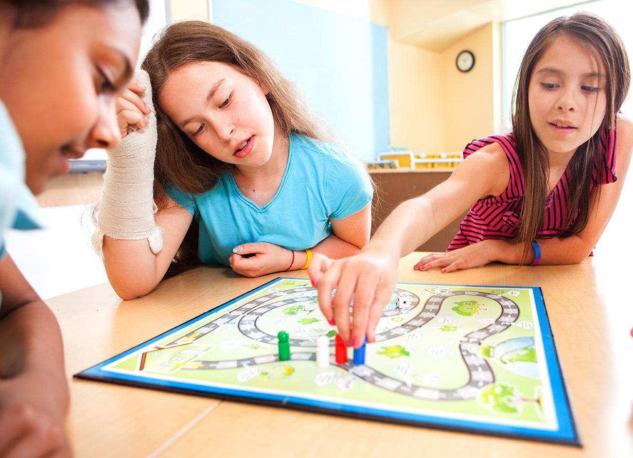 Foto de 3 garotas jogando um jogo de tabuleiro. Uma delas está manuseando um peão azul (crédito: diane39 – iStock)
