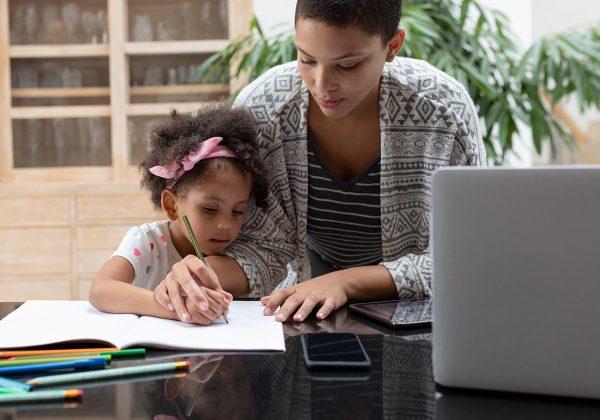 Foto de uma mulher ajudando uma menina a escrever com um lápis em um caderno em cima de uma mesa.