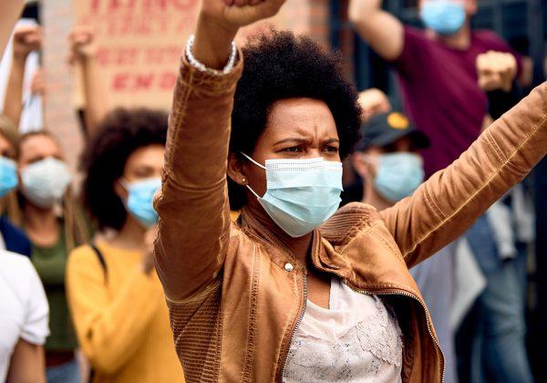 Foto de uma mulher negra usando máscara de proteção no rosto com os braços levantados em sinal de protesto. Ao fundo, há pessoas segurando cartazes e com os braços levantados.