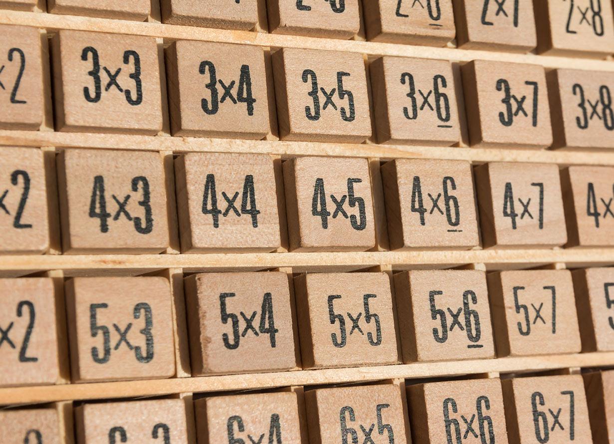 Foto de uma tabela de madeira contendo cálculos da tabuada (crédito: Giorez – iStock)