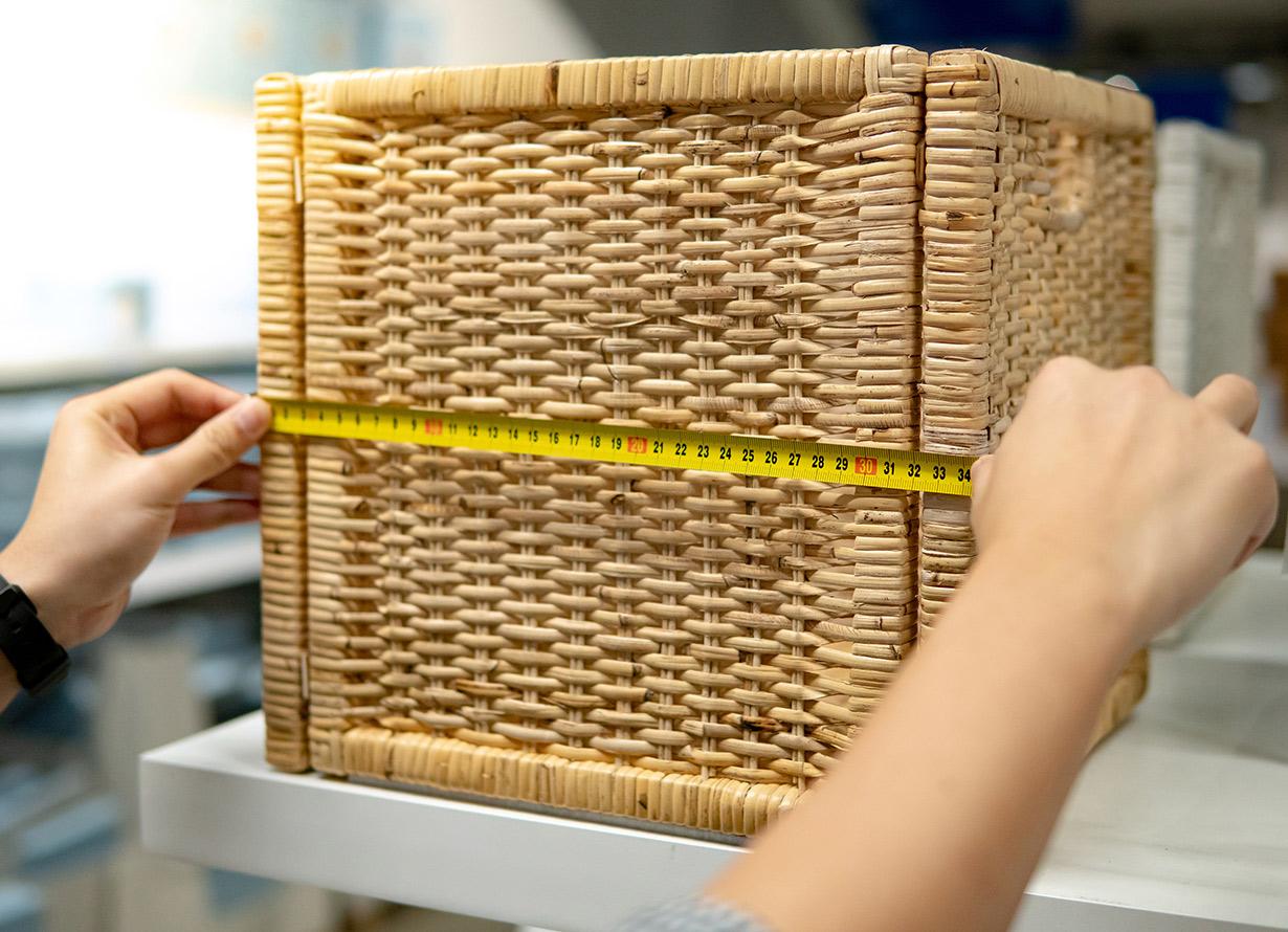 Foto de mãos medindo uma caixa de vime com uma trena (crédito Zephyr18 – iStock)