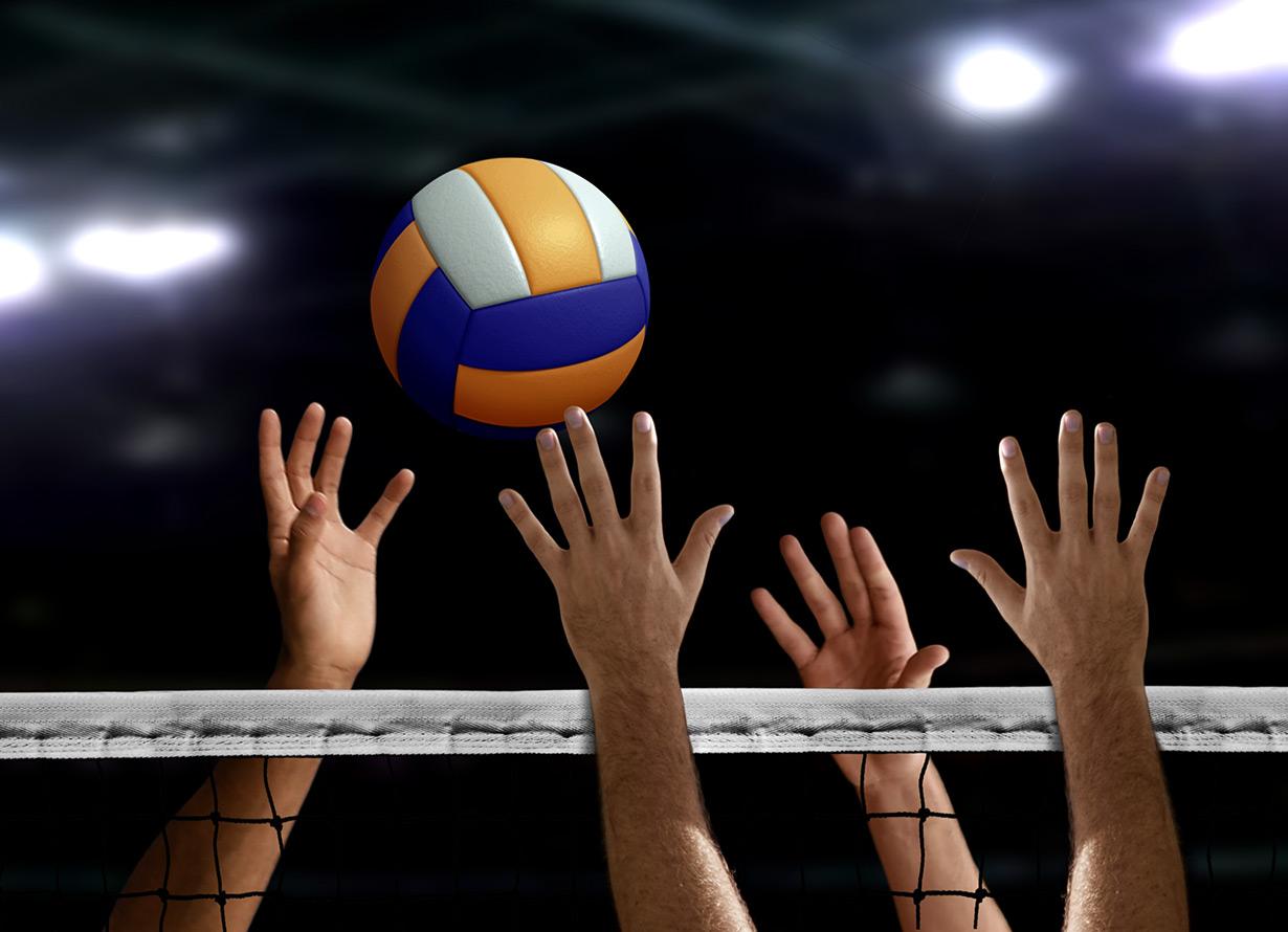 Foto em detalhe de mãos tentando alcançar uma bola de vôlei. No meio delas, há uma rede (crédito: razihusin – iStock)