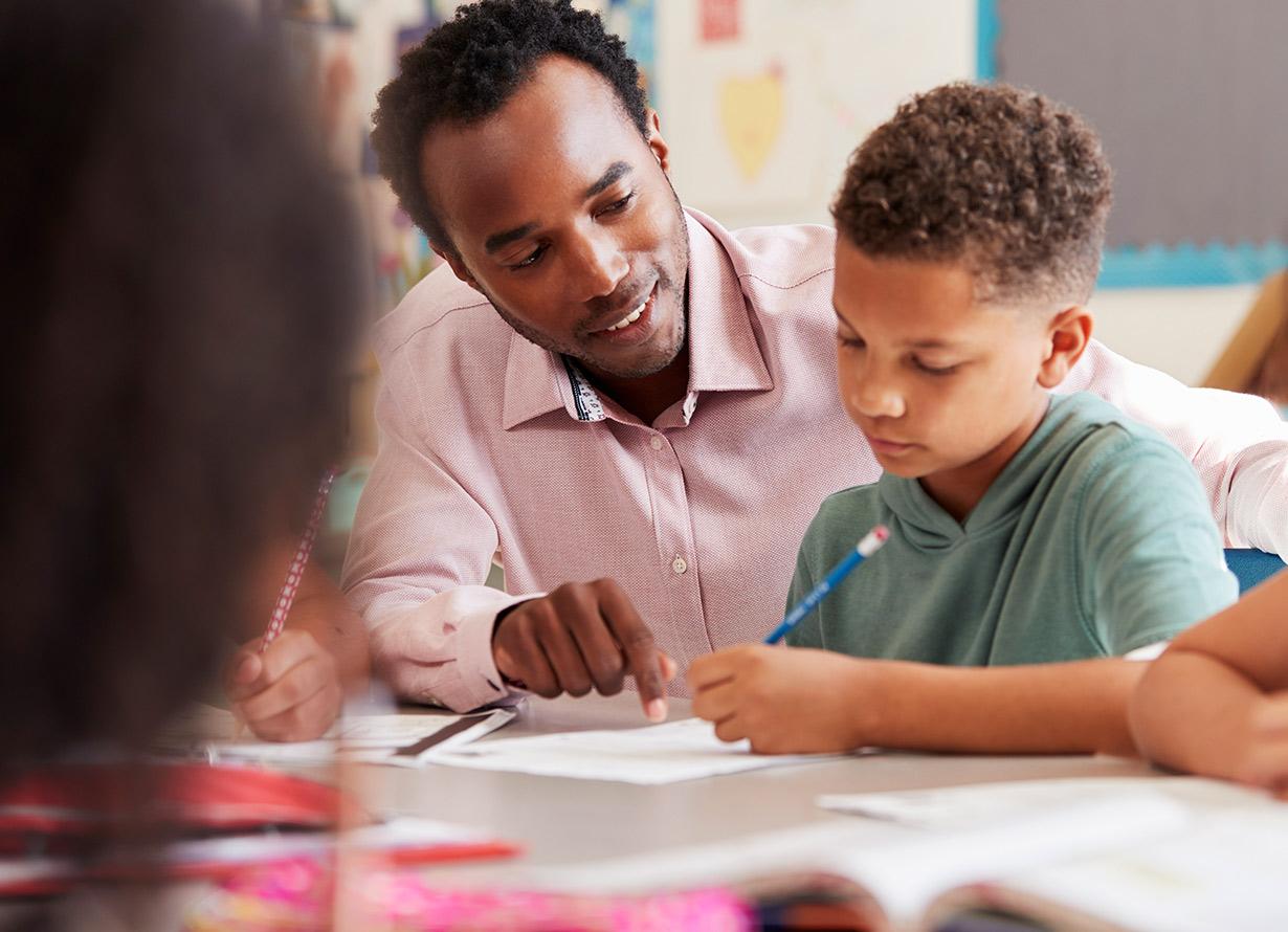 Foto em detalhe de um professor auxiliando um menino que escreve em um caderno (crédito: monkeybusinessimages – iStock)