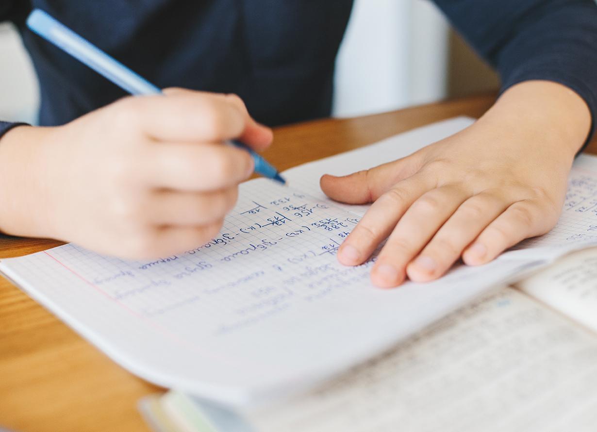 Foto em detalhe de mãos escrevendo em um caderno. Nas páginas, há diversas contas matemáticas (Crédito: Switlana Symonenko – iStock)