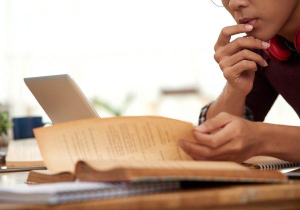 Foto em detalhe de uma pessoa negra de fones de ouvido folheando um livro antigo e com páginas amareladas
