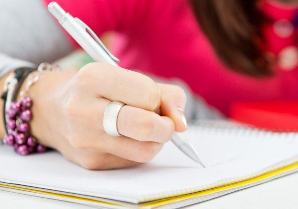 Foto em detalhe de mão escrevendo com uma lapiseira em um caderno