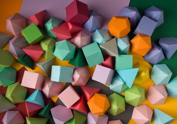 Foto vista de cima de sólidos platônicos de origami modular em cima de uma superfície colorida.
