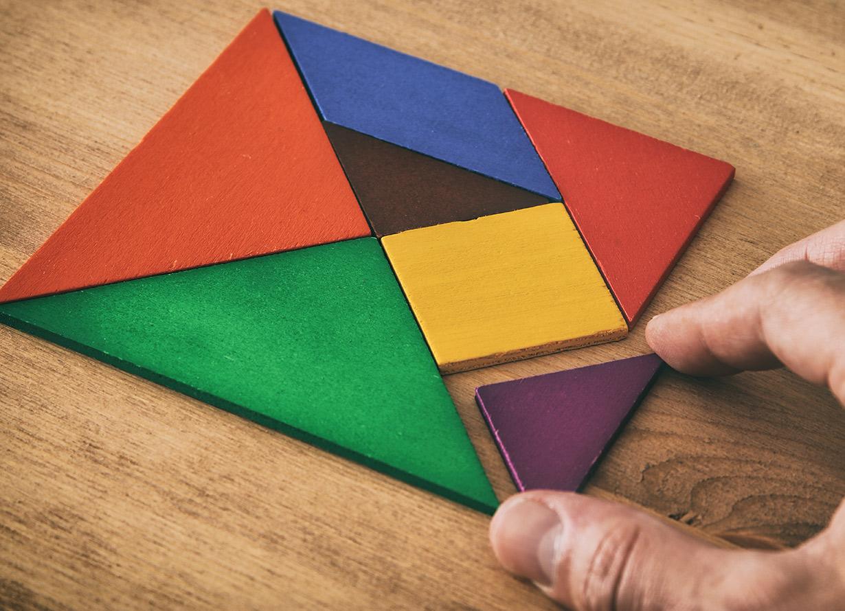 Foto em detalhe de mão manuseando uma peça de tangram