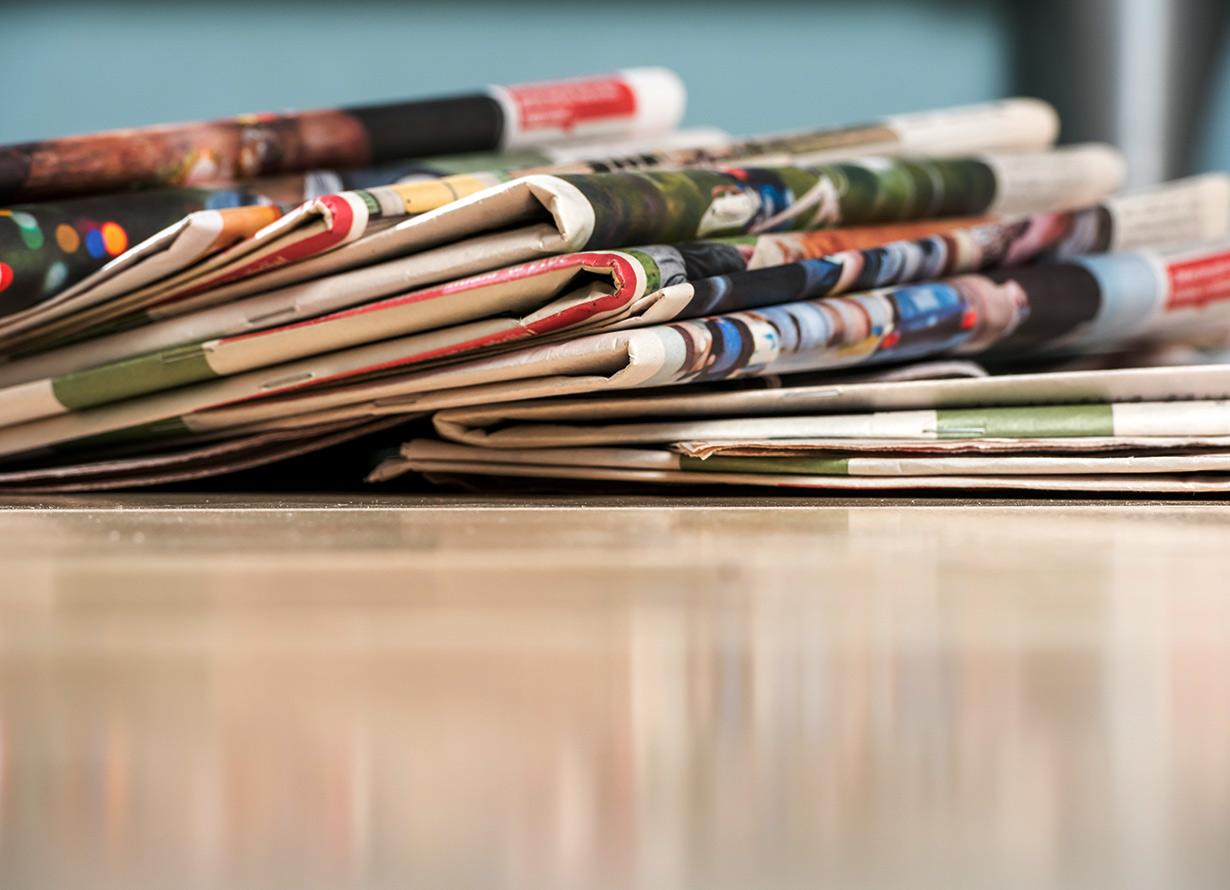 Foto de uma pilha torta de jornais sobre uma mesa