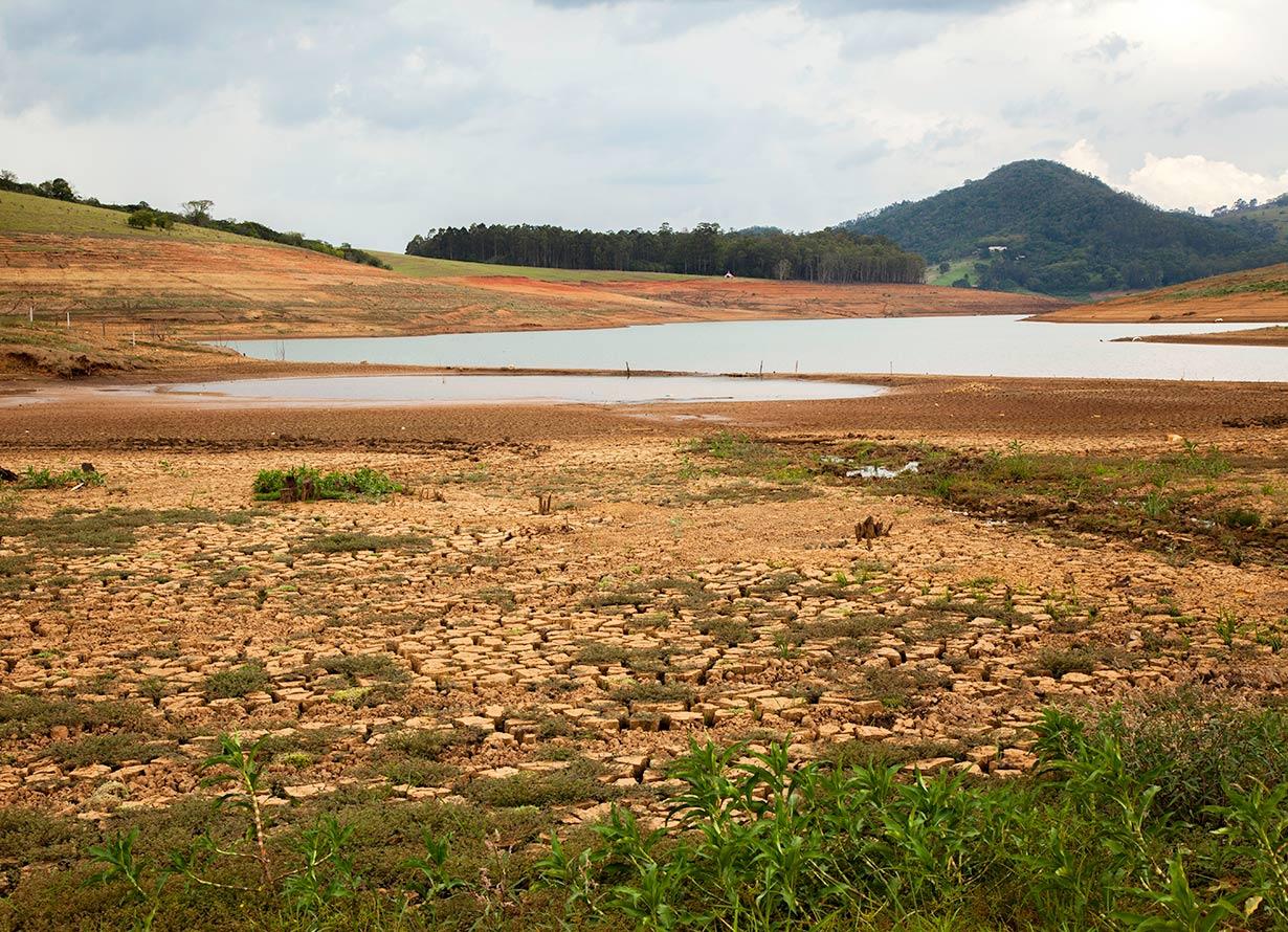 Foto em plano aberto de uma represa do sistema Cantareira. O reservatório está praticamente vazio mostrando um solo ressecado (crédito: TacioPhilip – iStock)