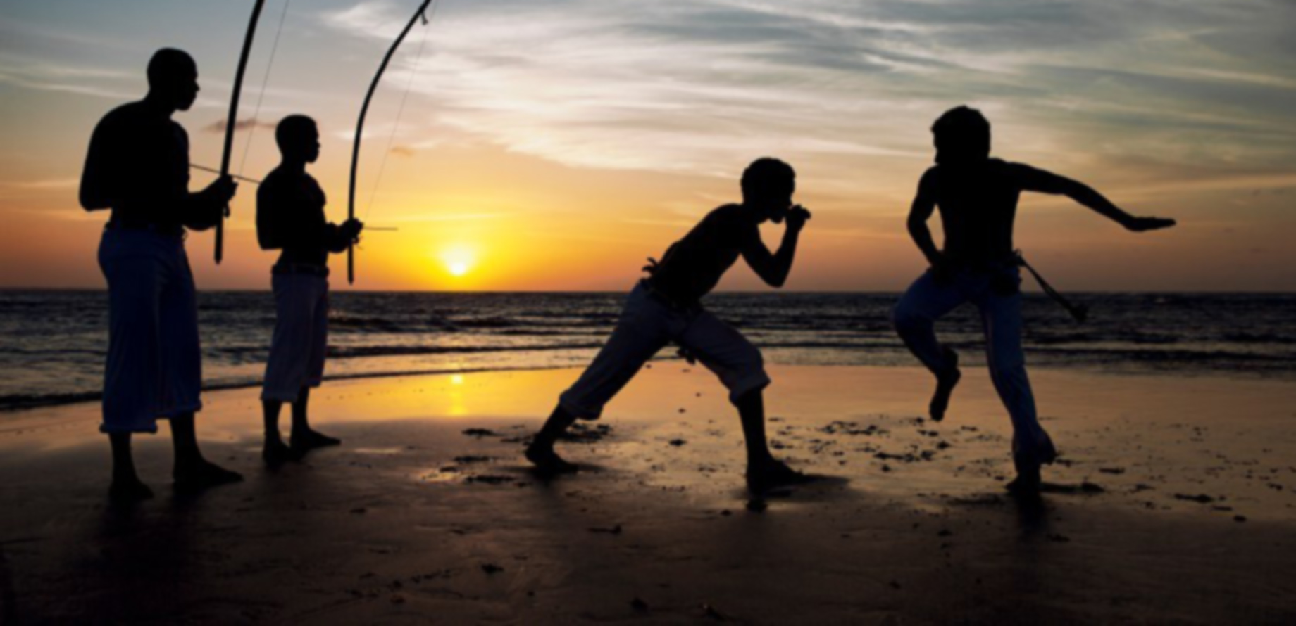 Foto de 2 garotos jogando capoeira na beira do mar ao entardecer