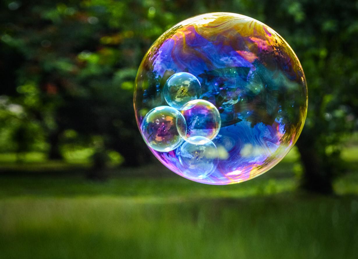 Foto de uma grande bolha de sabão com bolhas menores dentro dela. Ao fundo, há uma área verde arborizada