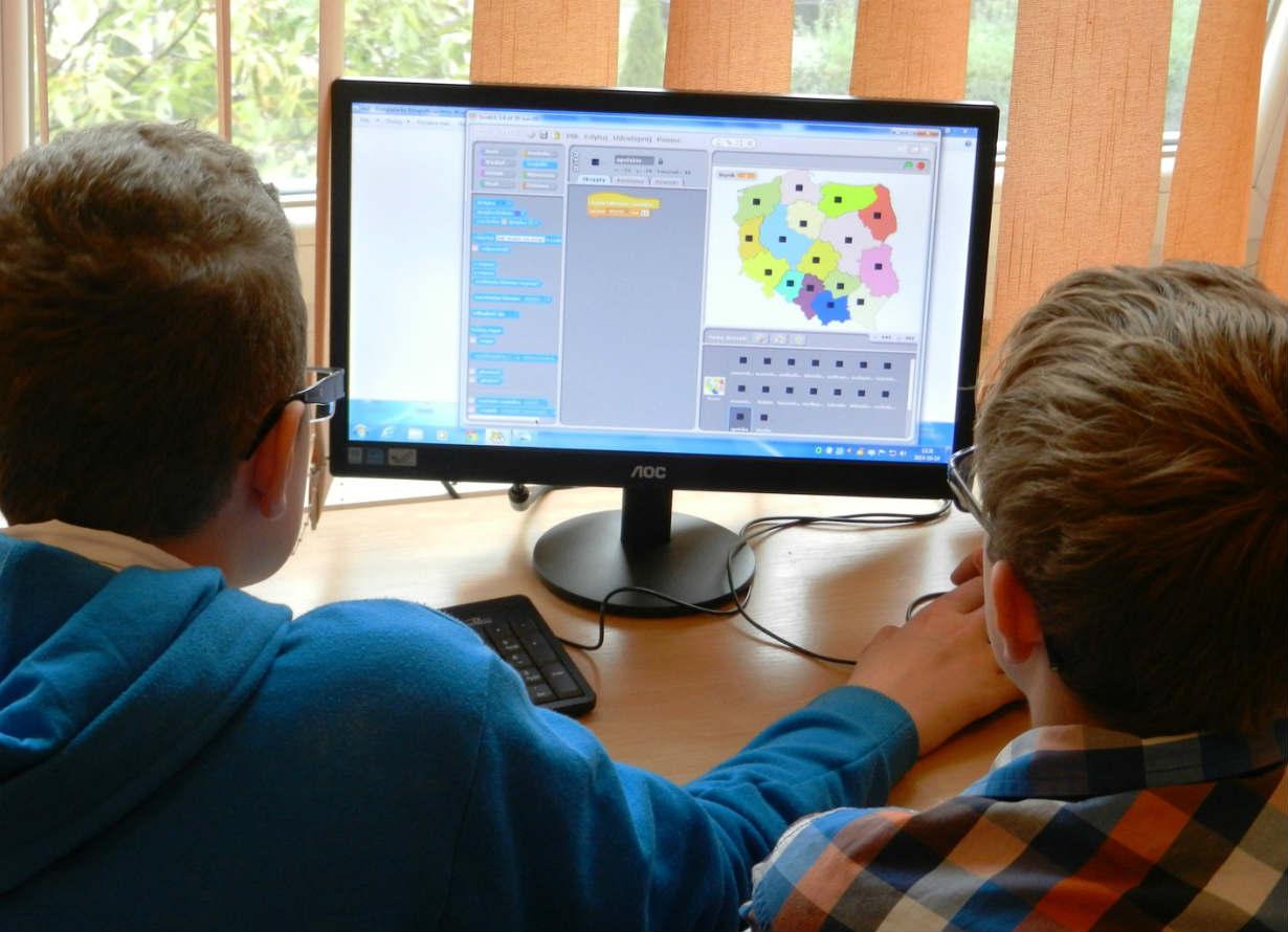 Foto de dois garotos sentados visto de costas. Eles estão olhando para a tela do computador.