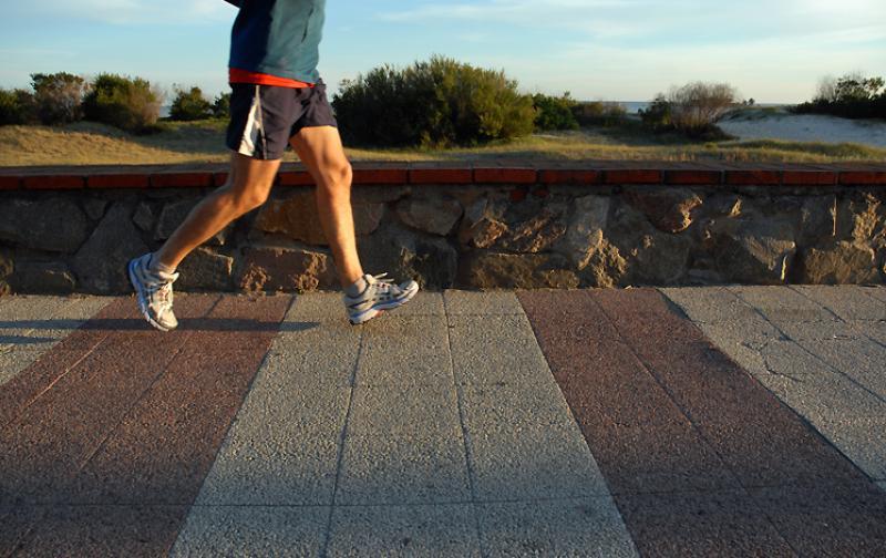 Foto em detalhe das pernas de um homem de lado, correndo