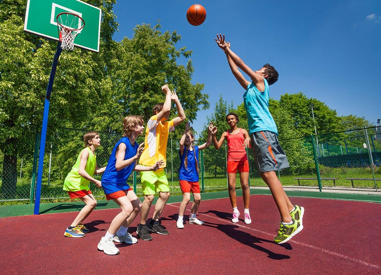 Foto de 6 crianças jogando basquete ao ar livre (crédito: SerrNovik – iStock)