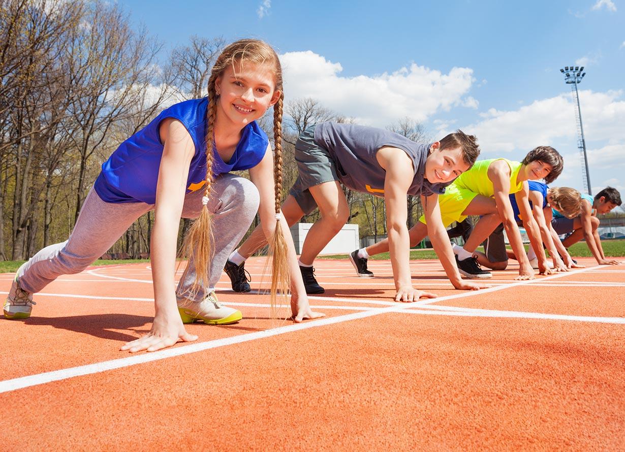 Foto de 5 crianças agachadas em um pista de corrida (crédito: SerrNovik – iStock)