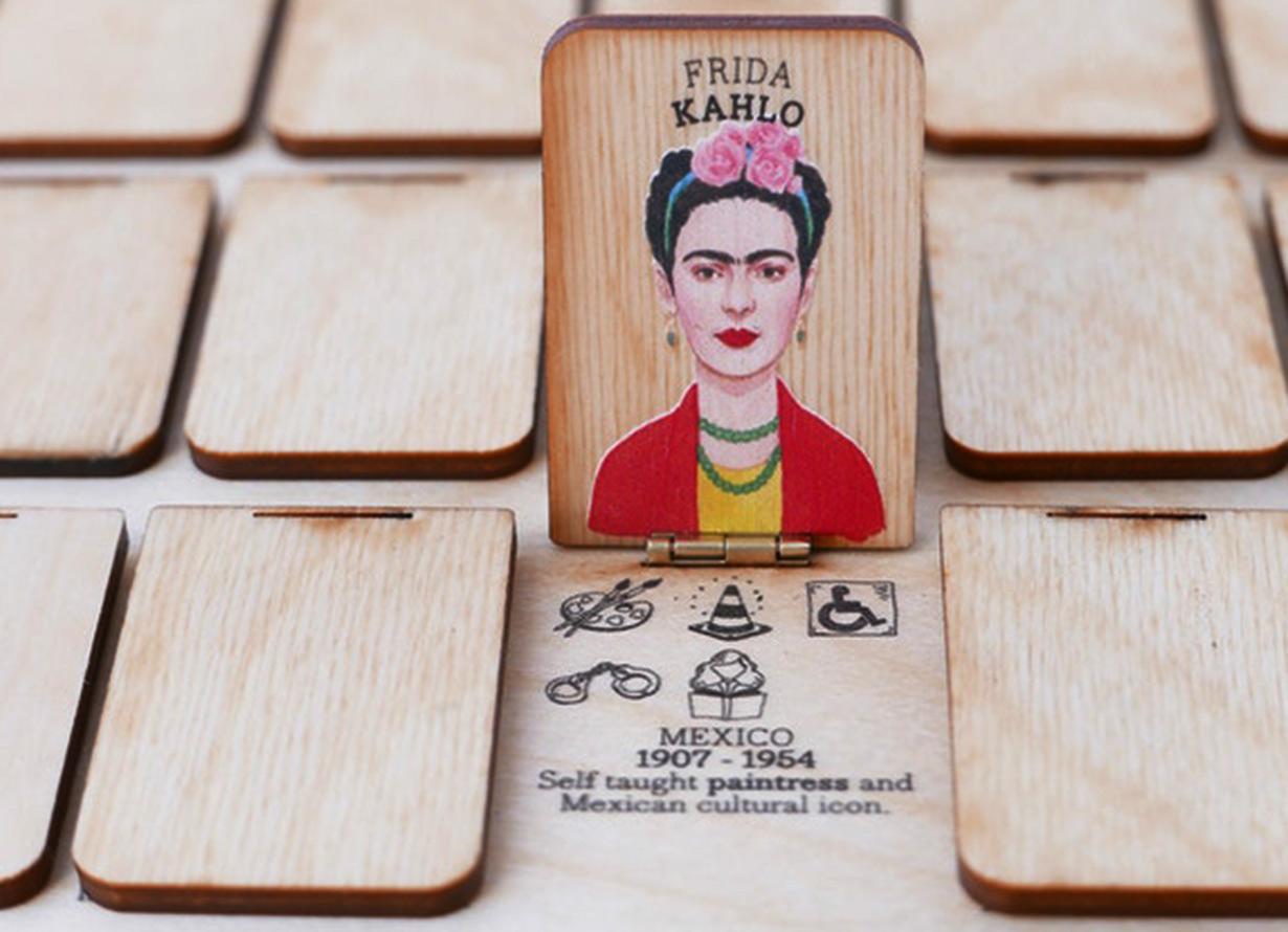 Foto do jogo who's she, com a figura de Frida Kahlo em um tabuleiro de madeira