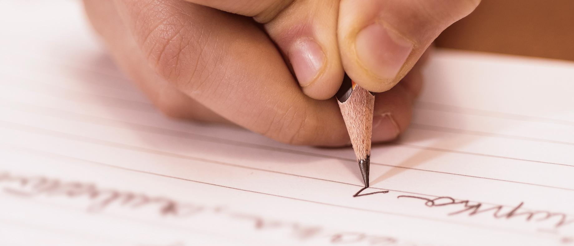 Foto em detalhe de mão escrevendo a lápis em um caderno (crédito: Victority – iStock)