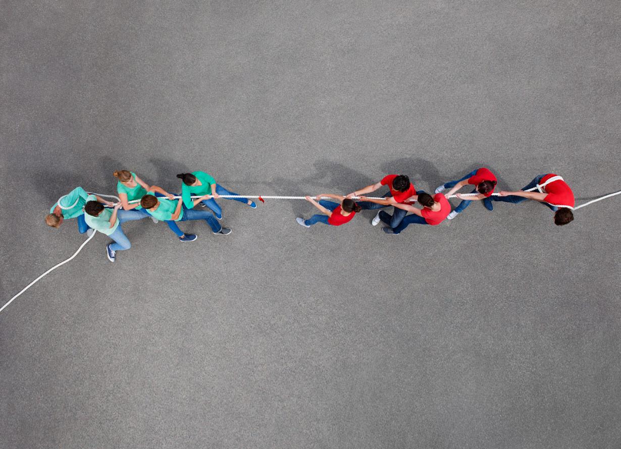 Foto vista de cima de dois times brincando de cabo de guerra, um em cada lado da corda (crédito: Photo_Concepts – iStock)