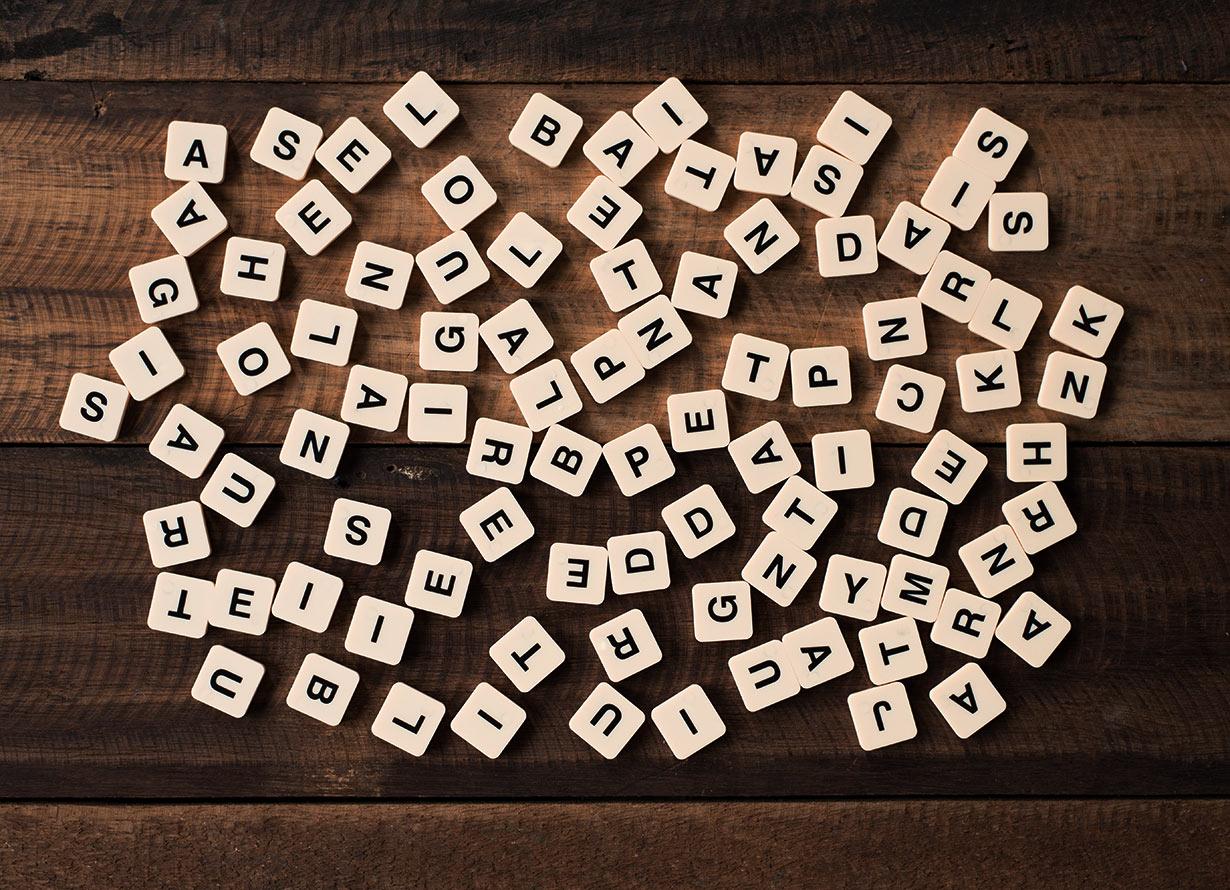 Foto vista de cima de peças com letras diversas sobre uma mesa de madeira escura (crédito: Hafiez Razali – iStock)