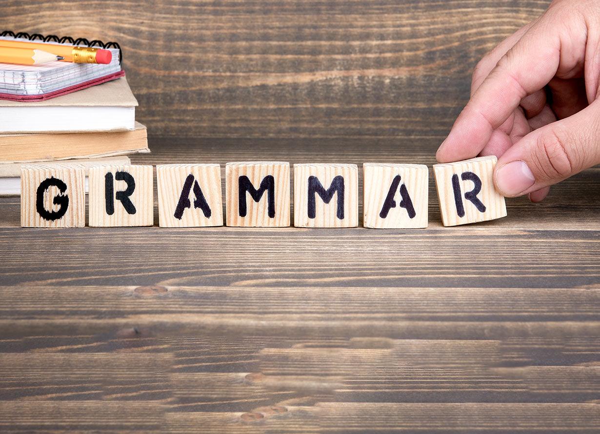 """Foto em detalhe de mãos manuseando cubos de madeiras com letras, formando a palavra em inglês """"grammar"""" (crédito: tumsasedgars – iStock)"""