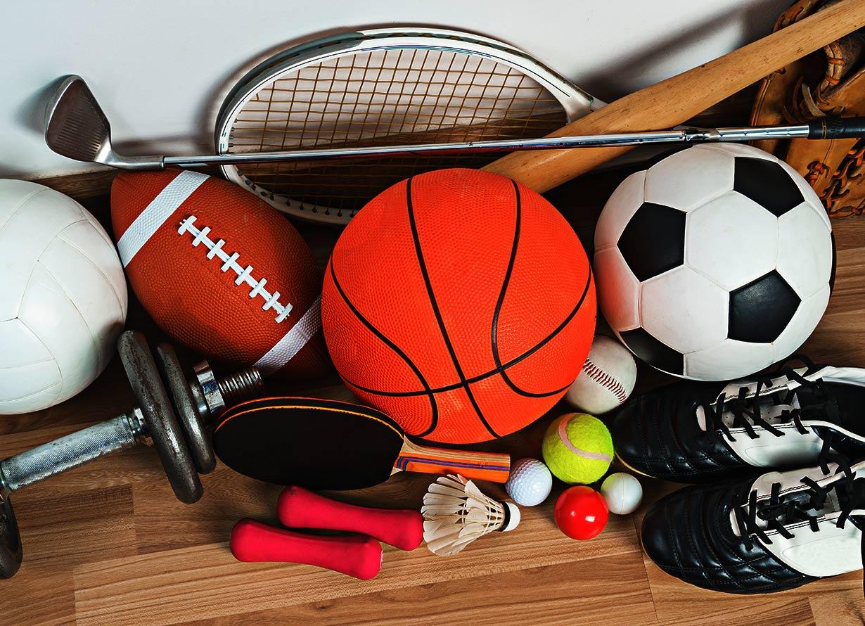 Foto de bolas de diversas modalidades esportivas ao lado de raquetes, alteres e um par de chuteiras pretas