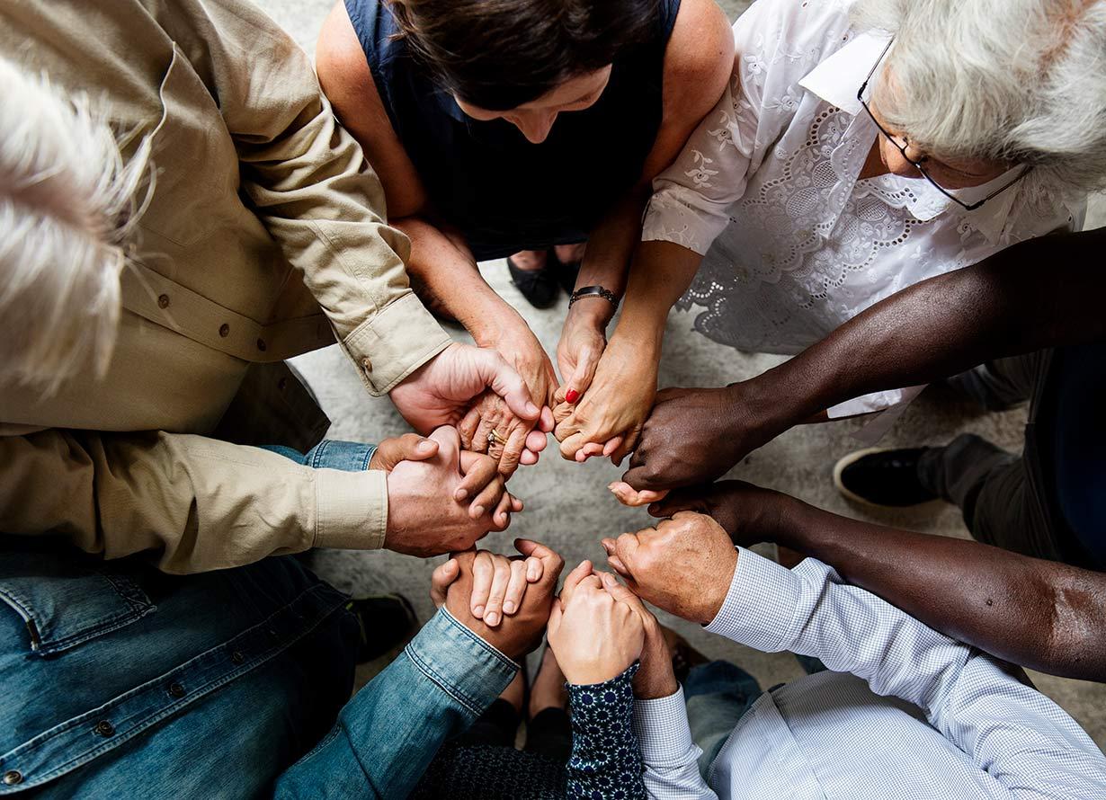 Foto em detalhe de pessoas diversas com as mãos dadas formando um círculo (Crédito: Rawpixel - iStock)